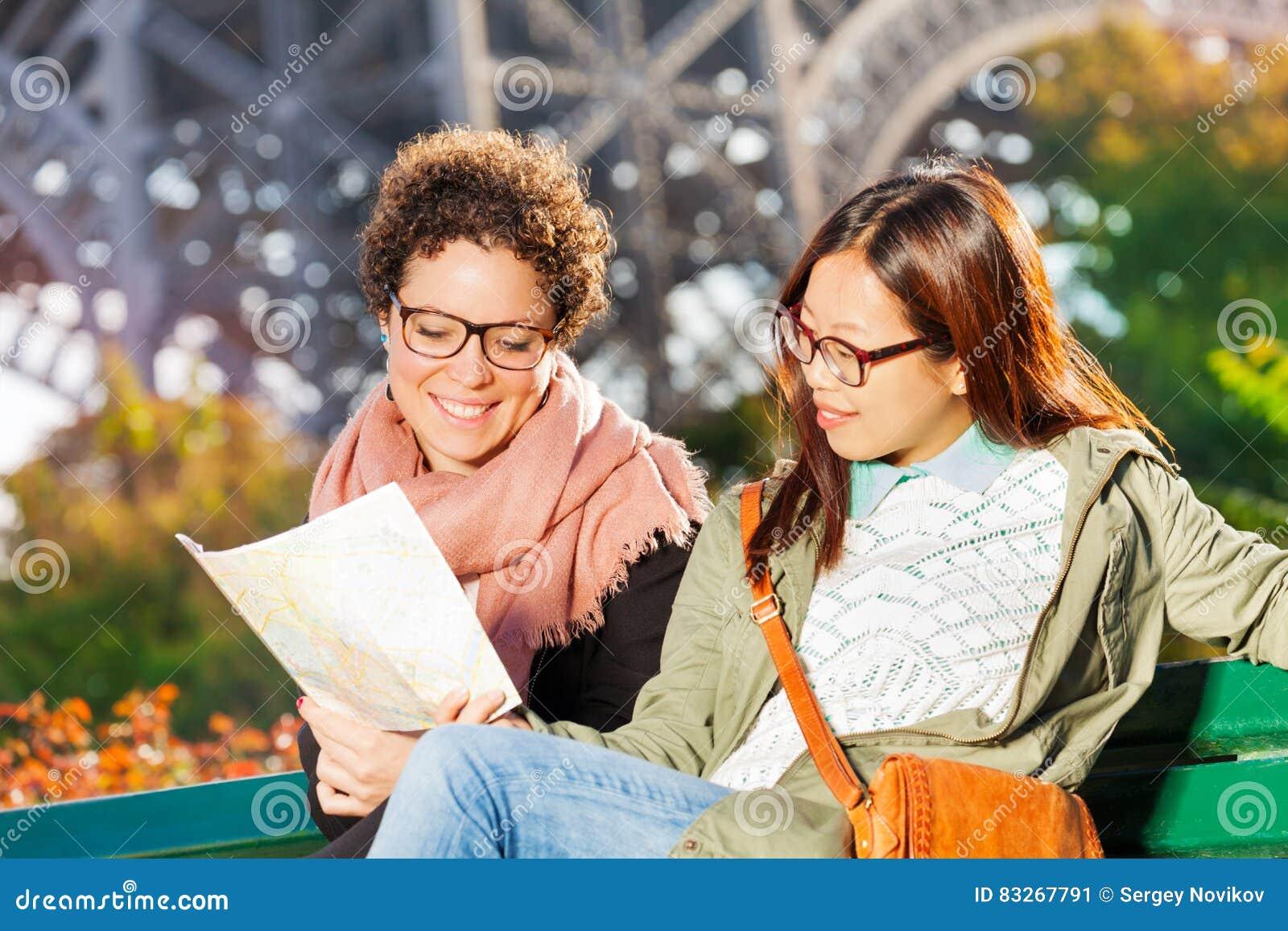 Zwei Frauen, die auf Bank mit Papierkarte von Paris sitzen