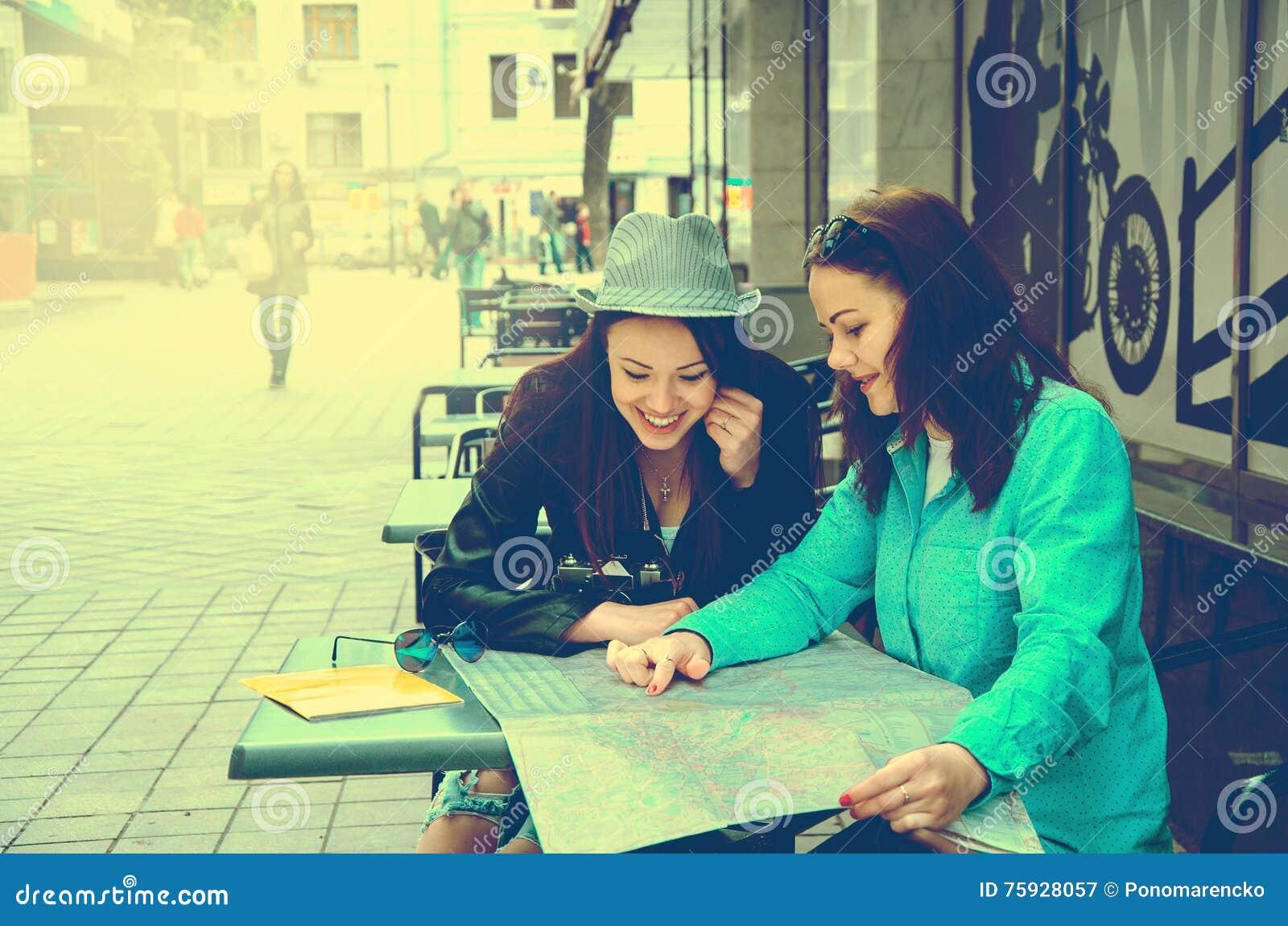 0ad2b739ead54b Zwei Frauen, Die An Einem Tisch Auf Der Straße Sitzen Stockbild ...