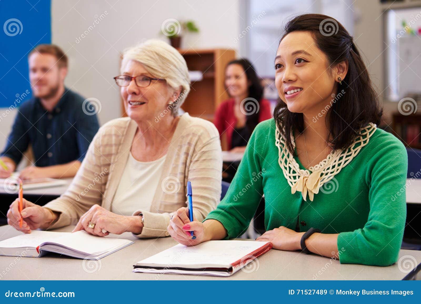 Zwei Frauen, die einen Schreibtisch an einer Erwachsenenbildungsklasse teilen, schauen oben