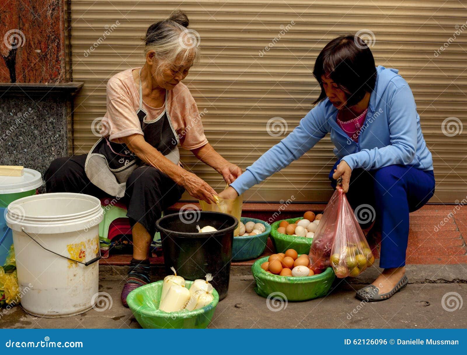 zwei frauen die frische eier im alten viertel von hanoi vietnam kaufen und verkaufen. Black Bedroom Furniture Sets. Home Design Ideas