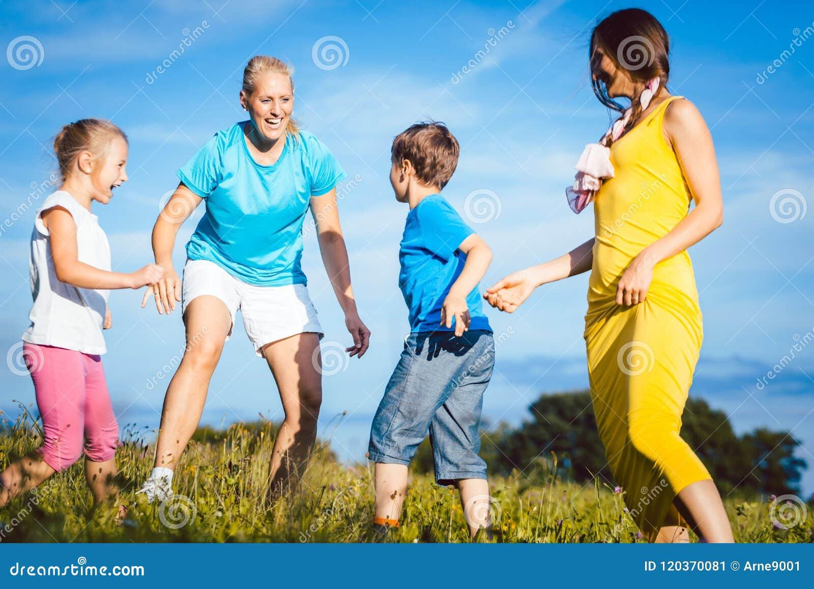 Zwei Frauen Mit Den Kindern, Die Tag Spielen Stockbild