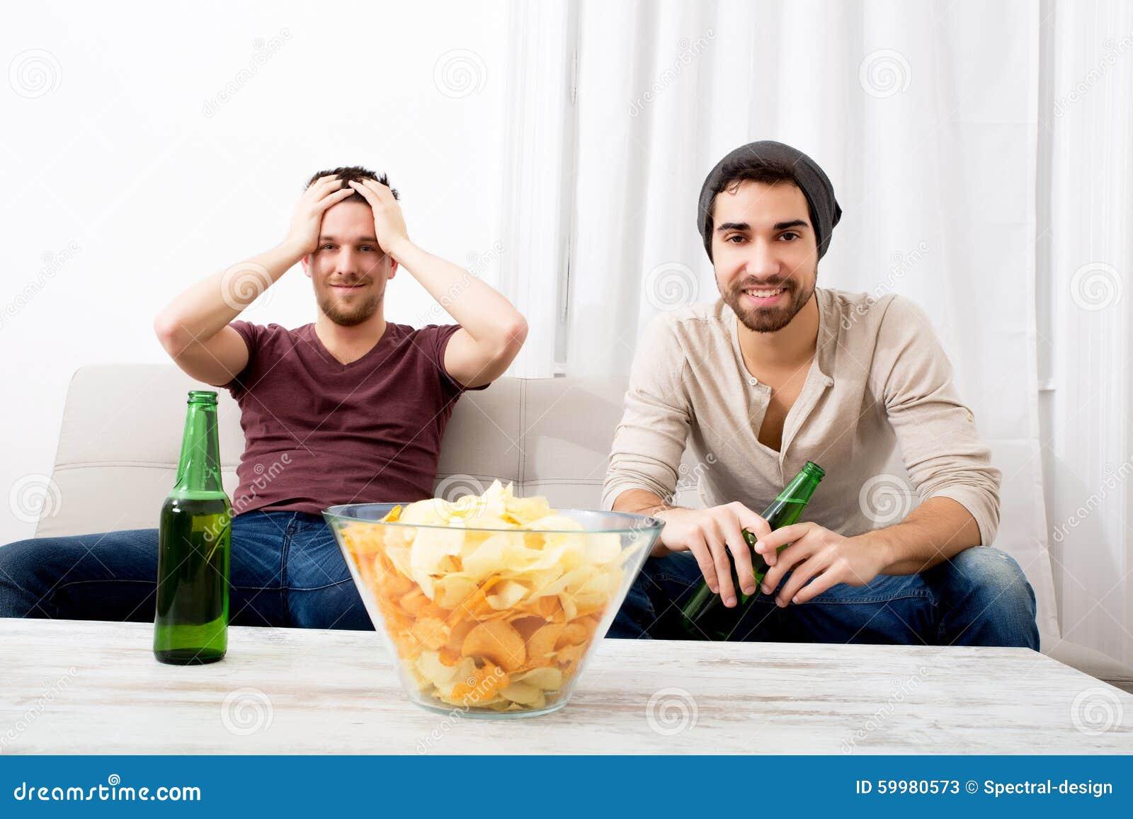 Zwei Freunde, die leidenschaftlich mit Bier und Chips fernsehen