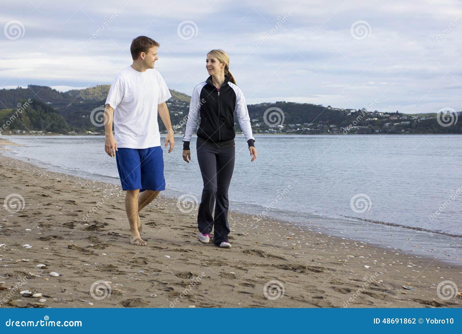 Zwei Freunde, die zusammen entlang Strand sprechen und gehen
