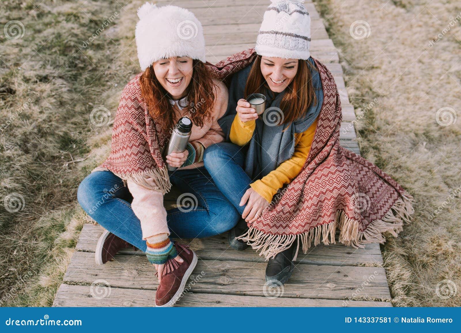 Zwei Freunde haben einen Sitz des Gelächters beim Trinken der Suppe, die mitten in der Wiese sitzt