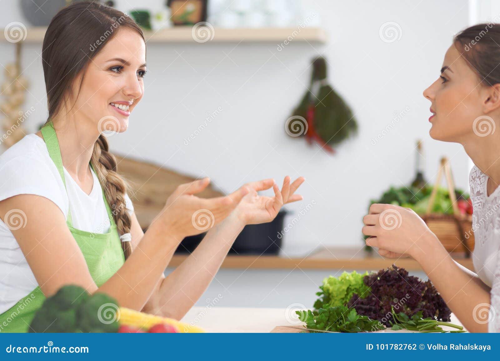 Zwei Freundinnen, die in der Küche beim Haben eines Vergnügensgespräches kochen Freundschaft und Chef-Cook-Konzept