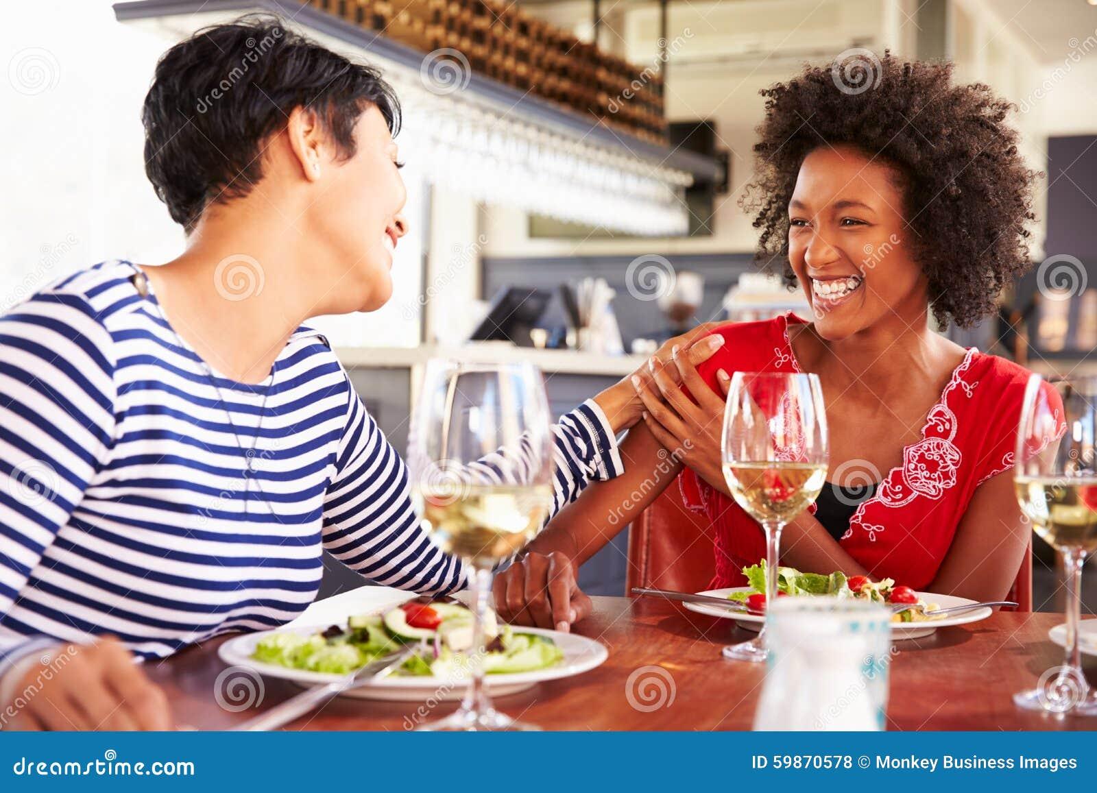 Zwei Freundinnen, die an einem Restaurant essen