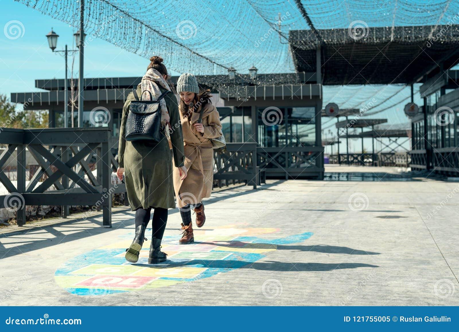 Zwei Freundinnen, die in einen Park gehen und Hopse auf der Pflasterung, Adoleszenz, Kindheit spielen