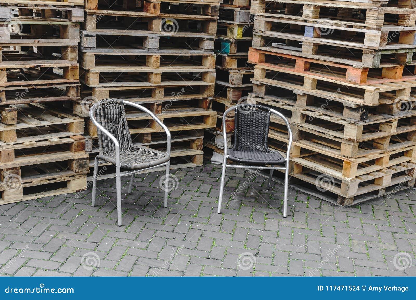 Zwei geflochtene Stühle gesetzt vor Stapeln Paletten