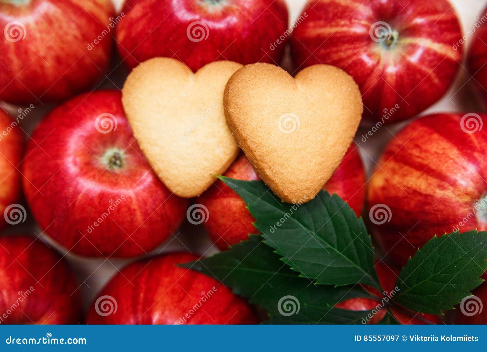 Zwei geformte Plätzchen des Herzens auf den roten Äpfeln