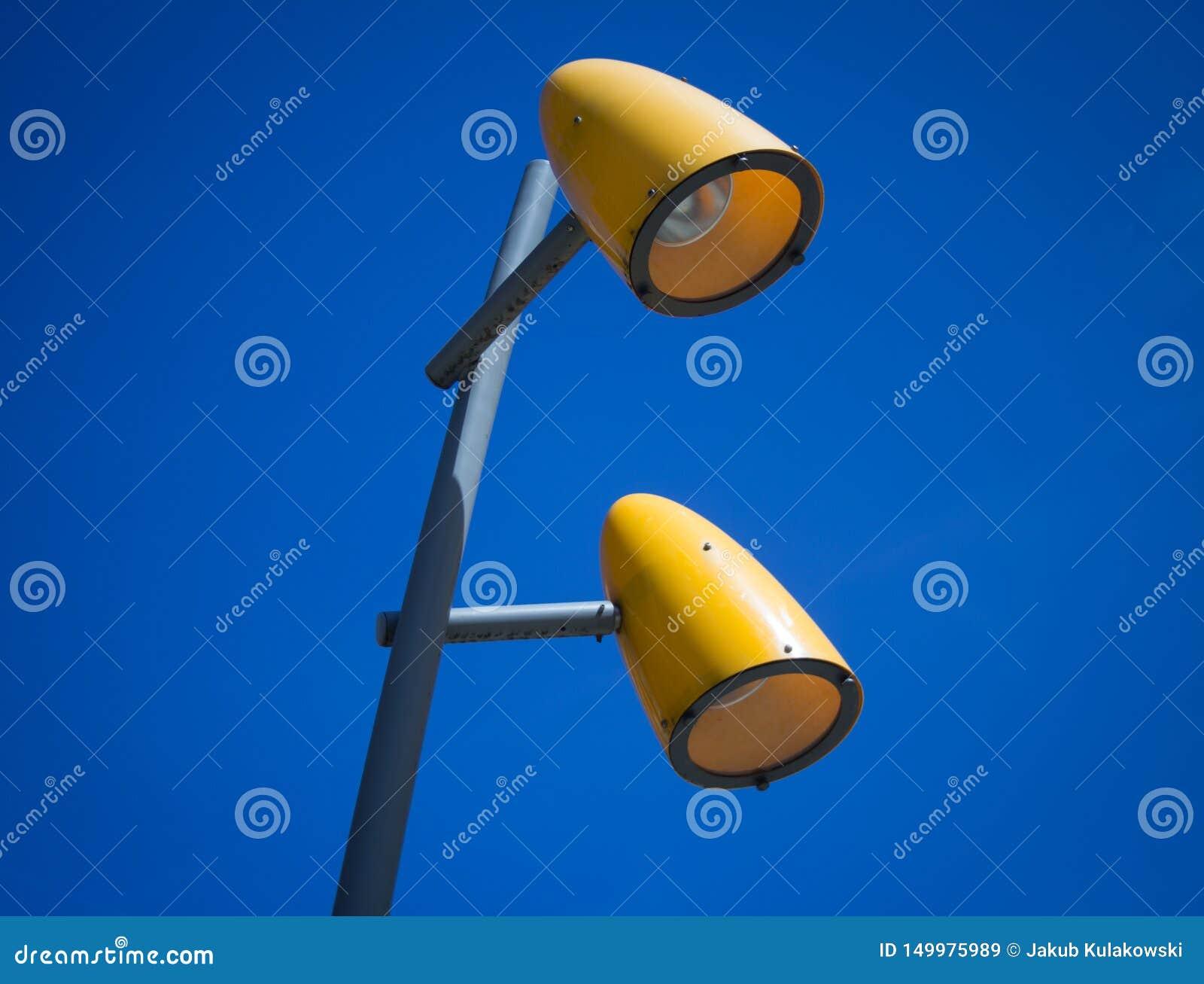 Zwei gelbe Straßenlaternen mit blauem Himmel