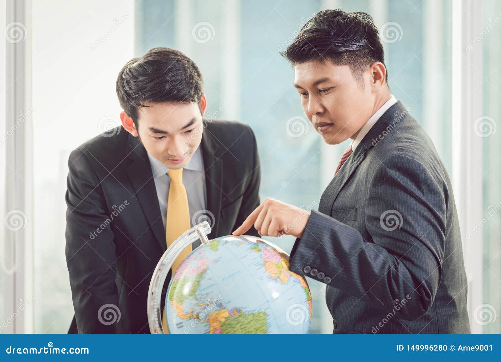 Zwei Geschäftsmänner, die Kugel betrachten