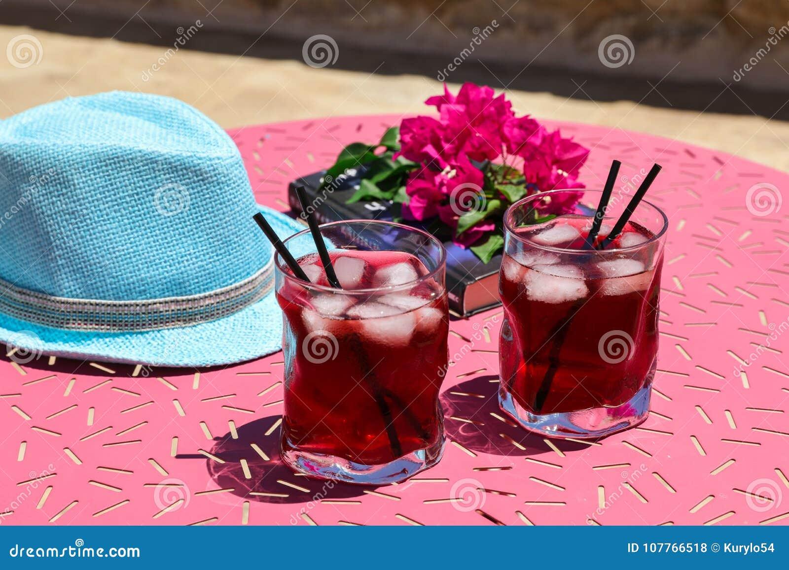 Zwei Gläser des roten Cocktails des Sommers mit Eis nahe bei einem Buch, ein Zweig des Bouganvillas blüht, blauer Hut auf einer r