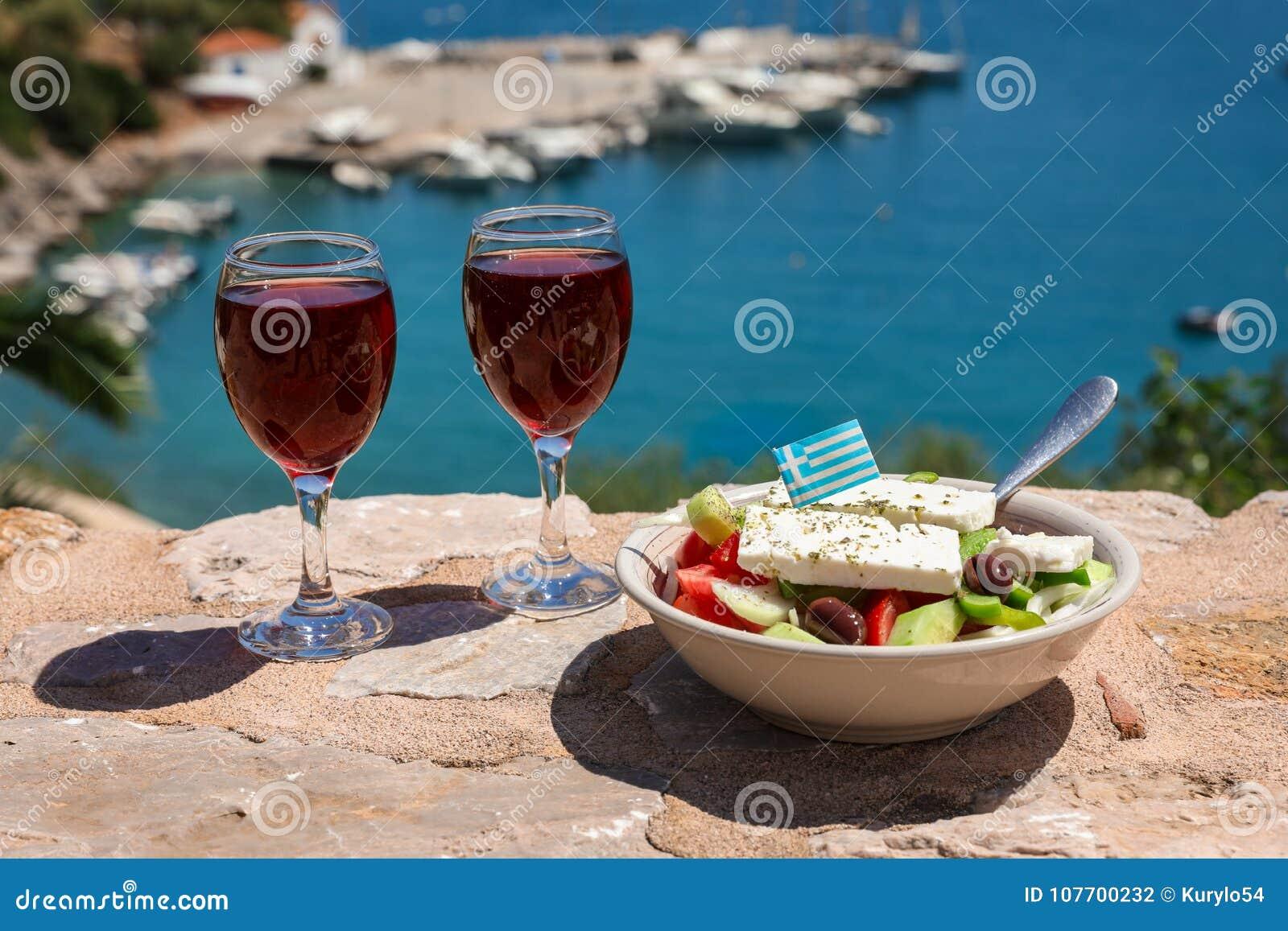 Zwei Gläser des Rotweins und der Schüssel griechischen Salats mit griechischer Flagge an durch die Seeansicht, griechisches Feier