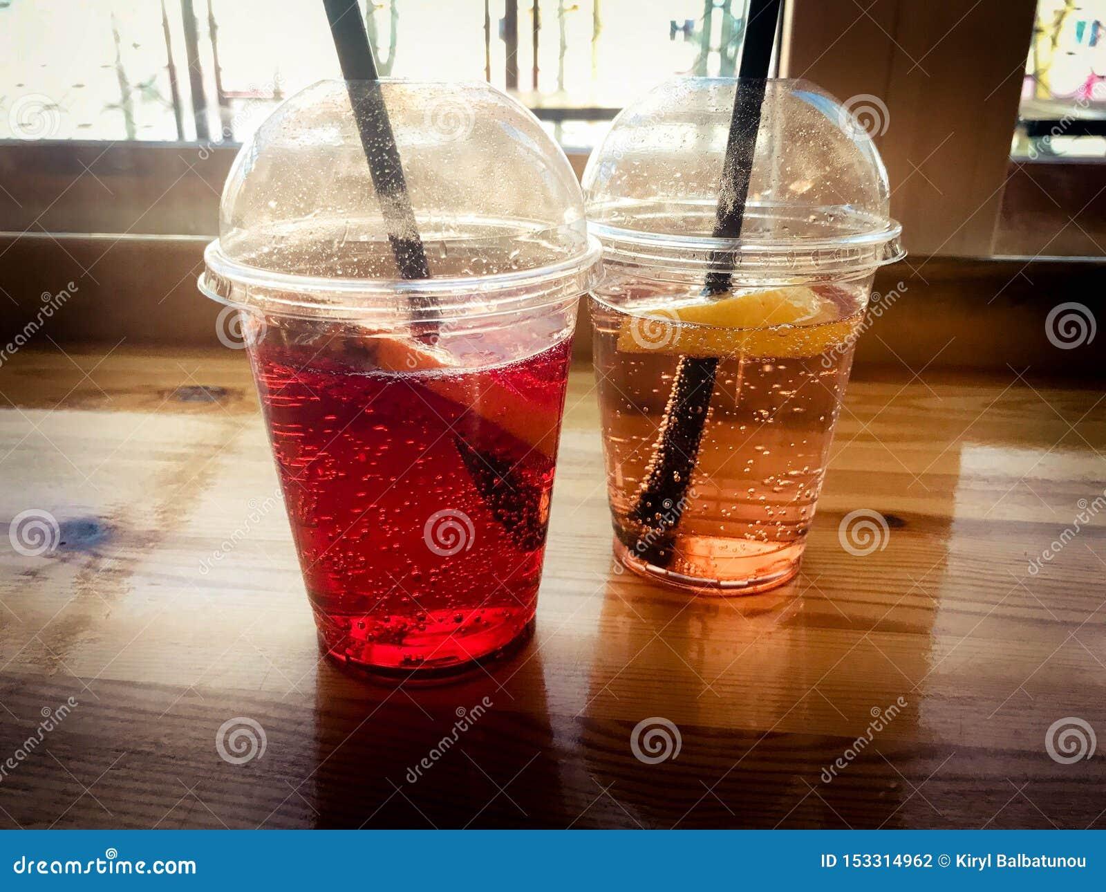 Zwei Gläser rote und gelbe erneuernde kalte geschmackvolle süße Himbeererdbeerkirschorange Pfirsichzitronen-Fruchtplastiklimonade