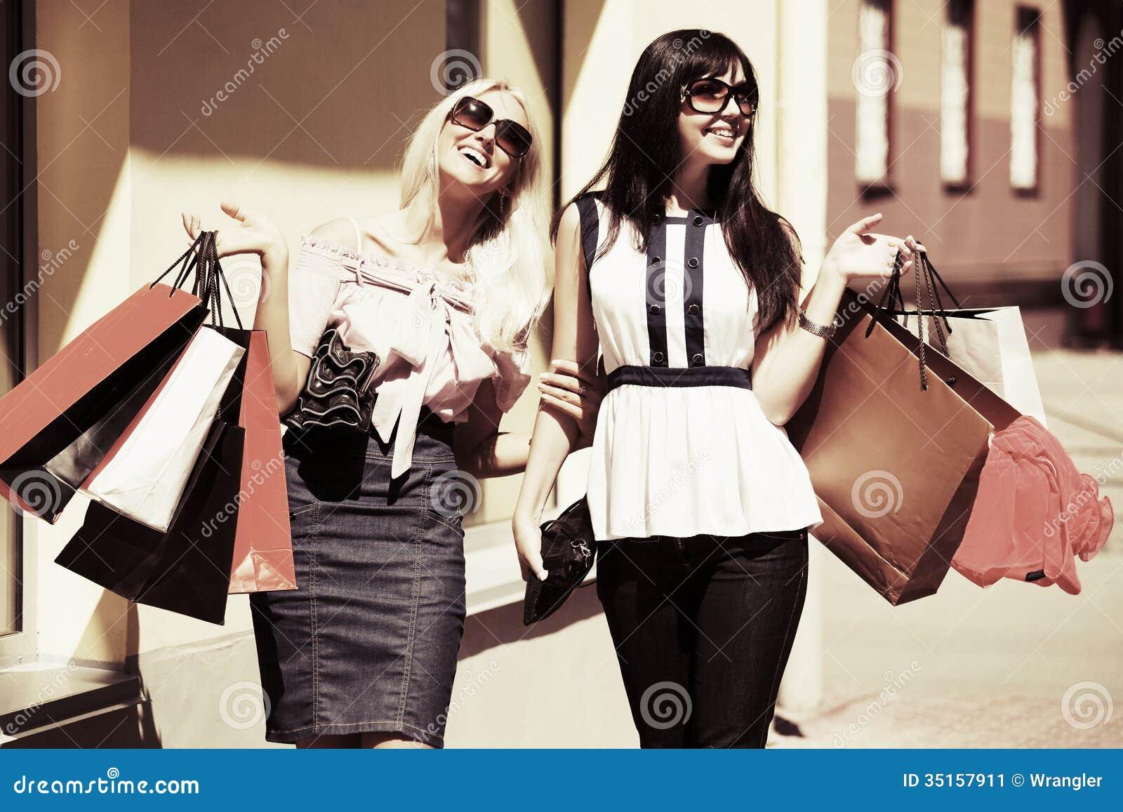 Zwei glückliche Frauen mit Einkaufstaschen