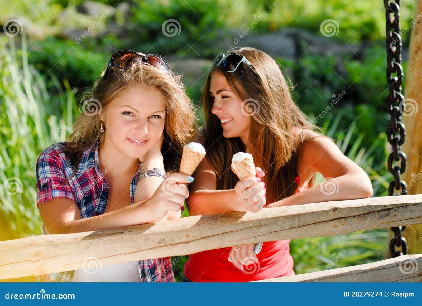 Zwei glückliche Freundinnen, die draußen Eiscreme essen