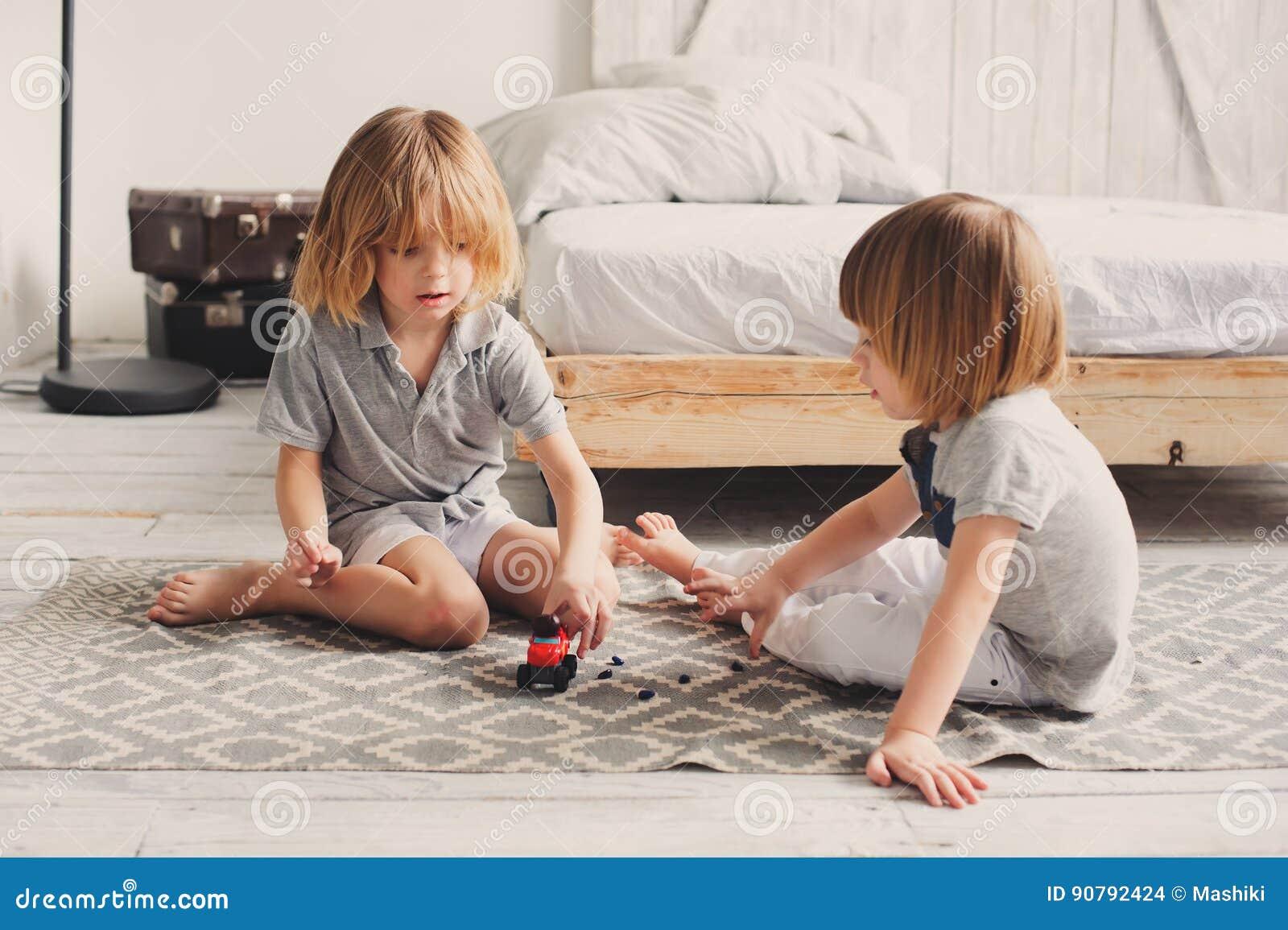 Zwei glückliche Geschwisterjungen, die zusammen zu Hause mit Spielzeugautos spielen