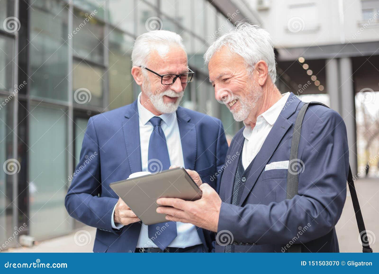 Zwei glückliche lächelnde ältere graue behaarte Geschäftsmänner, die an einer Tablette arbeiten