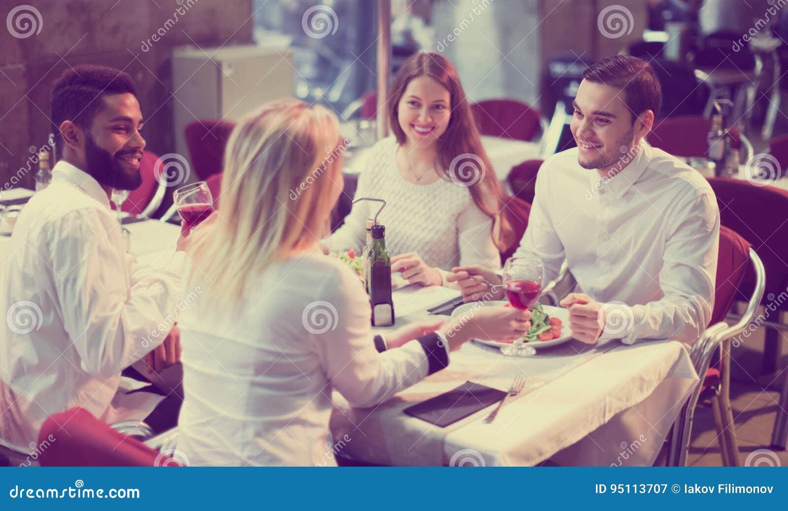 Zwei glückliche Paare, die Restaurant am im Freien sitzen