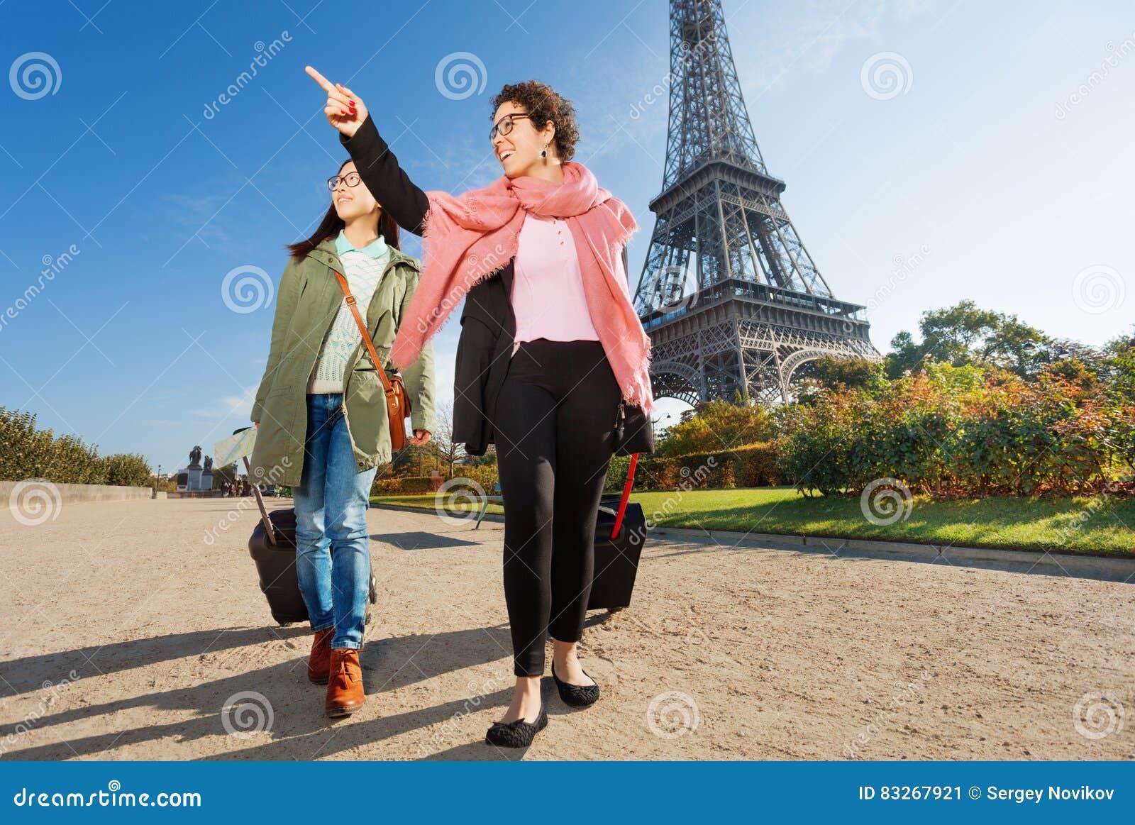 Zwei glückliche weibliche Touristen, die um Paris gehen