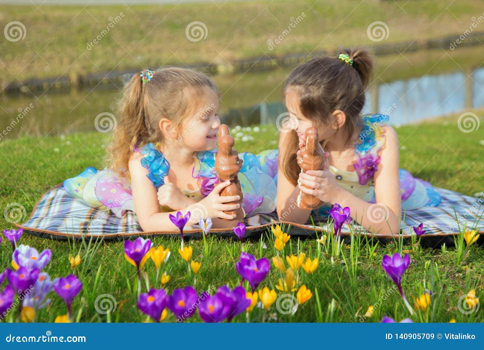 Zwei gleichmäßig gekleidete kleine Schwestern liegen unter den Blumen