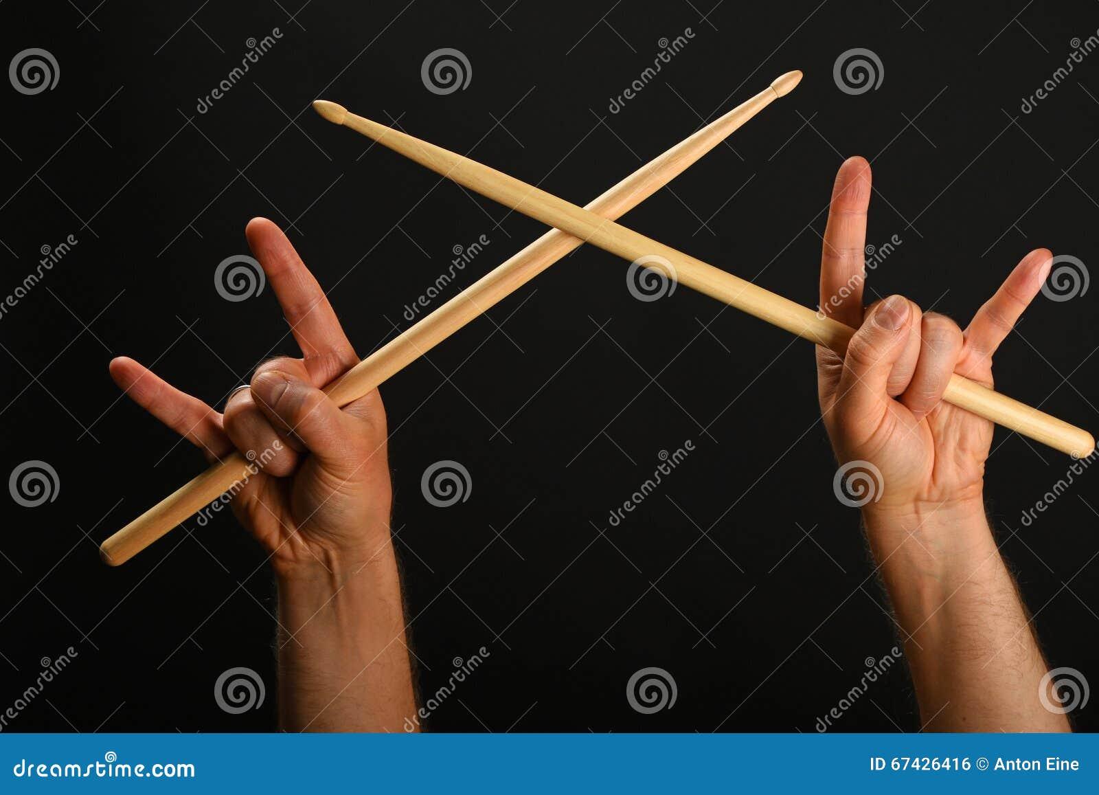 Zwei Hände mit gekreuzten Trommelstöcken und Teufelhörnern