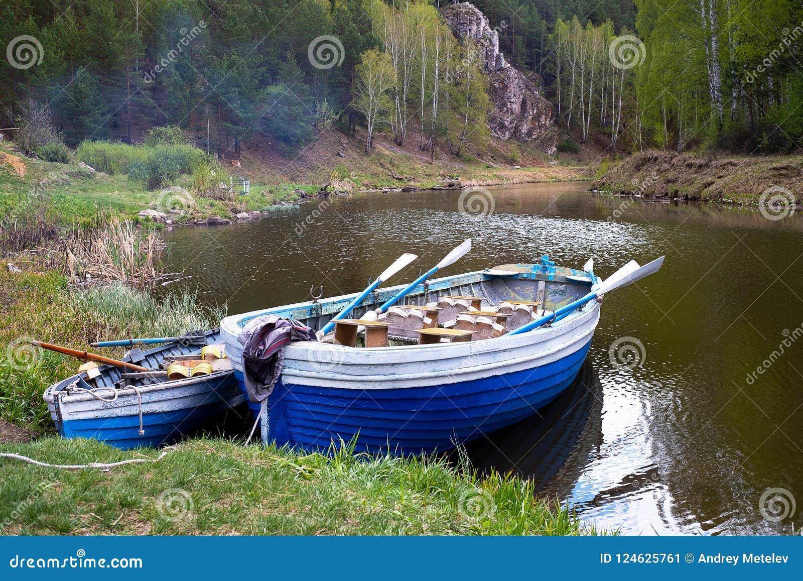 Zwei hölzerne Boote mit Rudern auf der Bank des Waldflusses, Wald