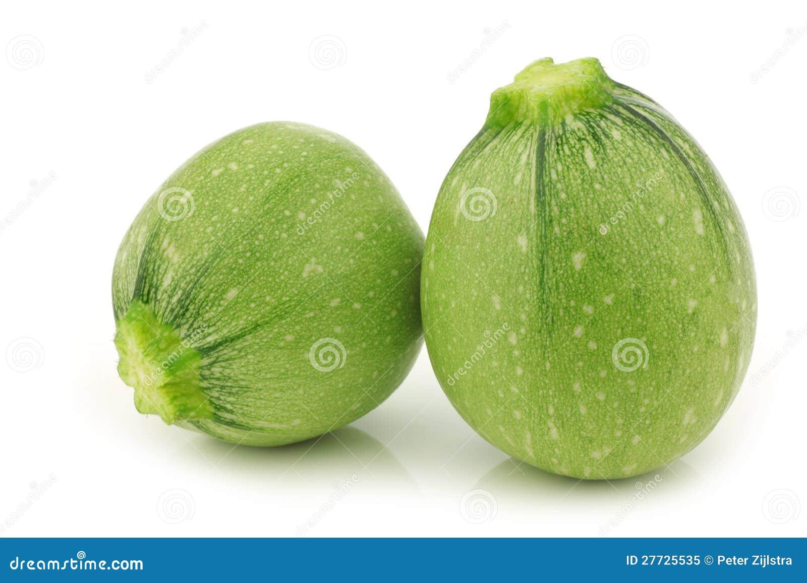 Zwei hellgrüne runde Zucchini
