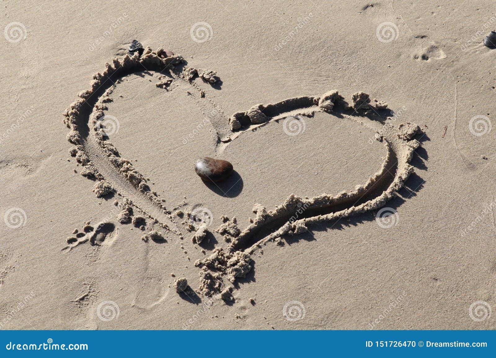Zwei Herzen als eins auf einem Strand