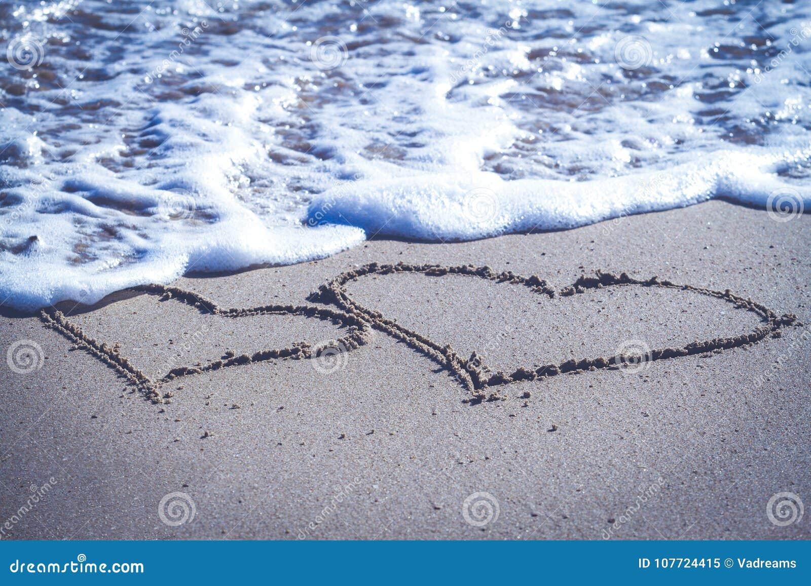 Zwei Herzen gezeichnet auf den Sand des Strandes und der blauen Meereswellen mit Schaum
