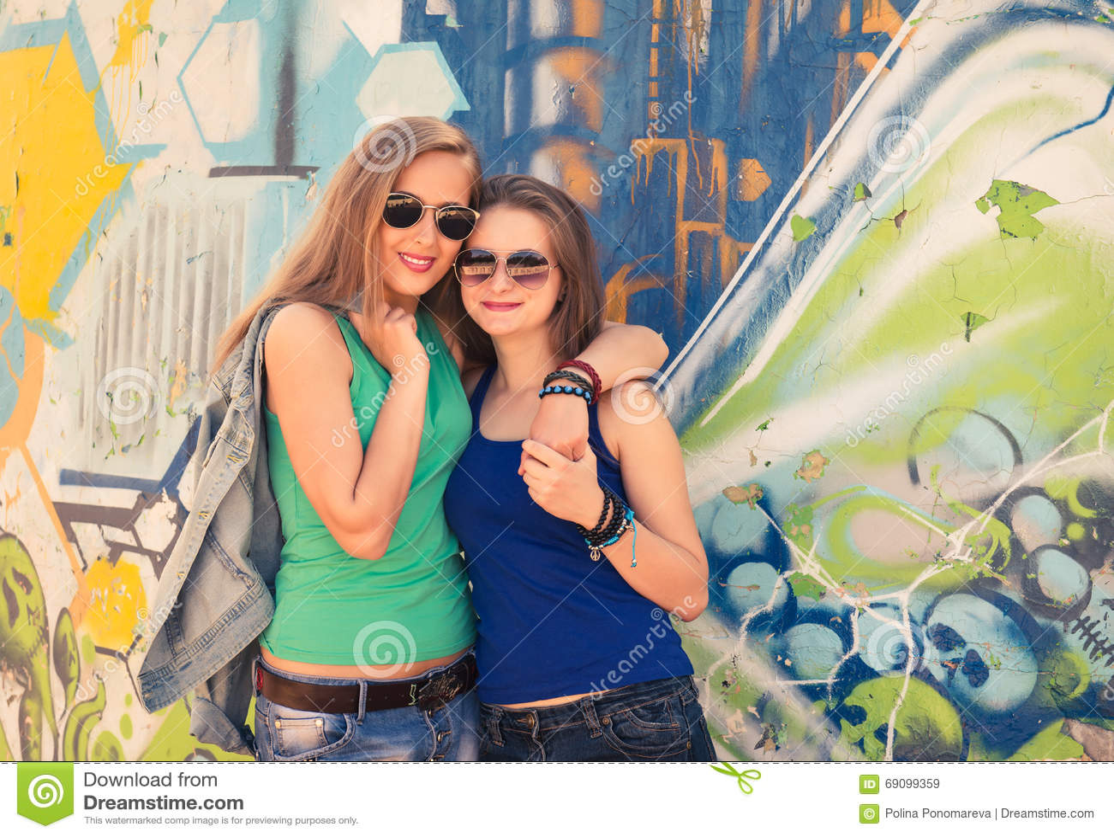 Zwei Hippie-Freundinnen des jungen jugendlich, die zusammen Spaßgraffiti haben