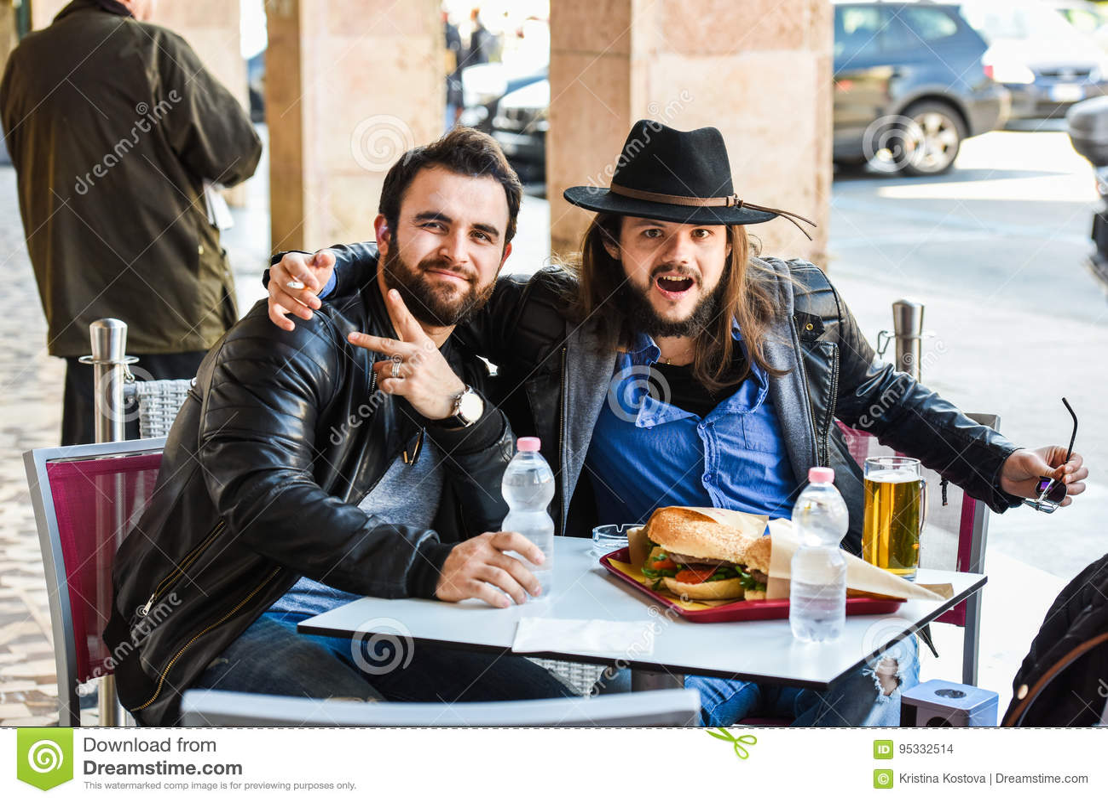 Zwei hungrige Freunde/Touristen essen draußen im offenen