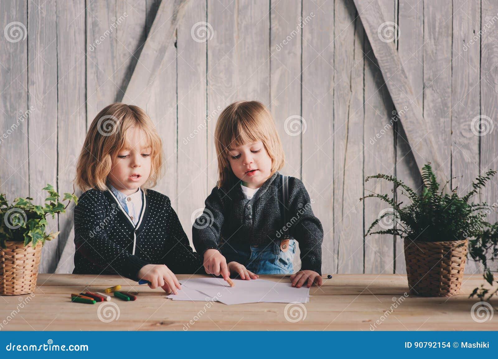 Zwei jüngere Brüder, die zusammen zu Hause zeichnen Glückliche Geschwister, die zusammen Zeit verbringen