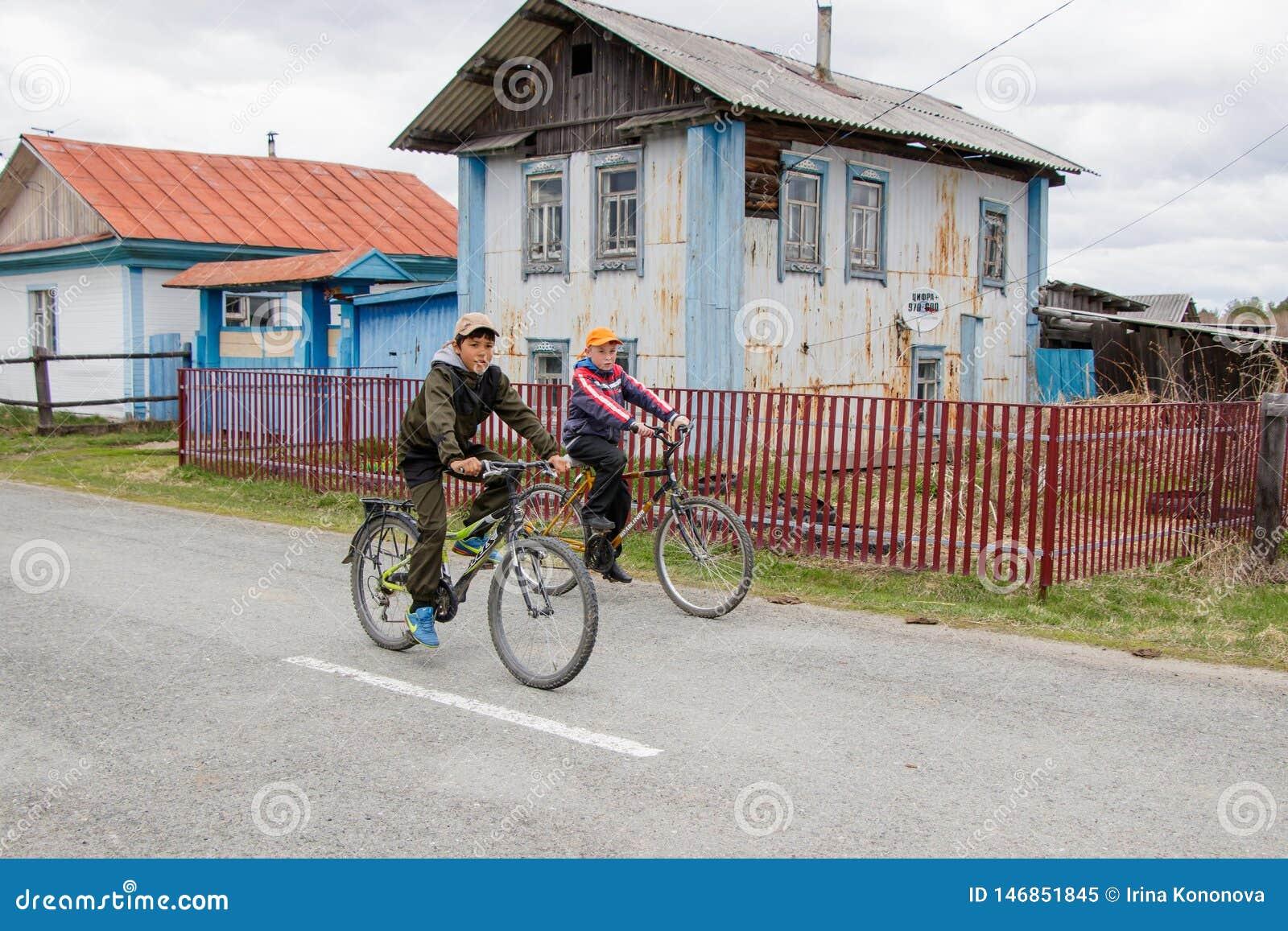 Zwei Jugendliche laufen auf Fahrrädern durch das Dorf hinter dem alten Haus