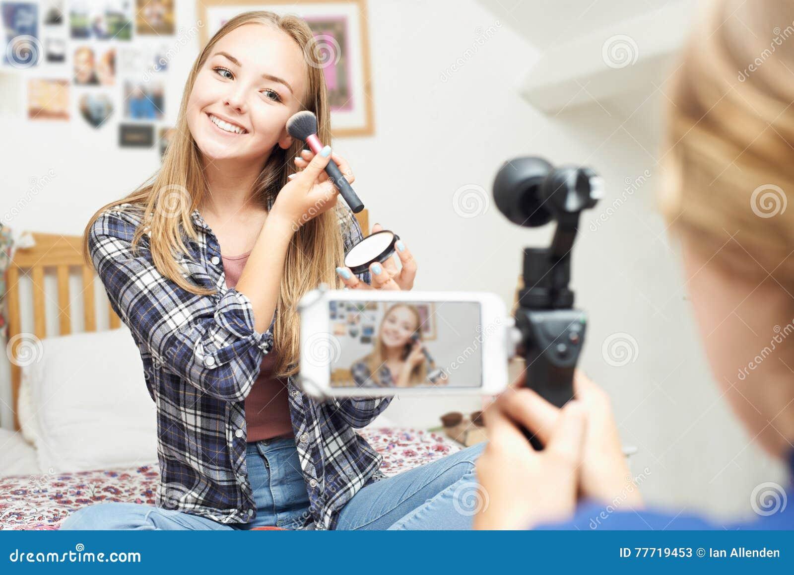Zwei Jugendlichen, die Schönheits-Blog im Schlafzimmer notieren