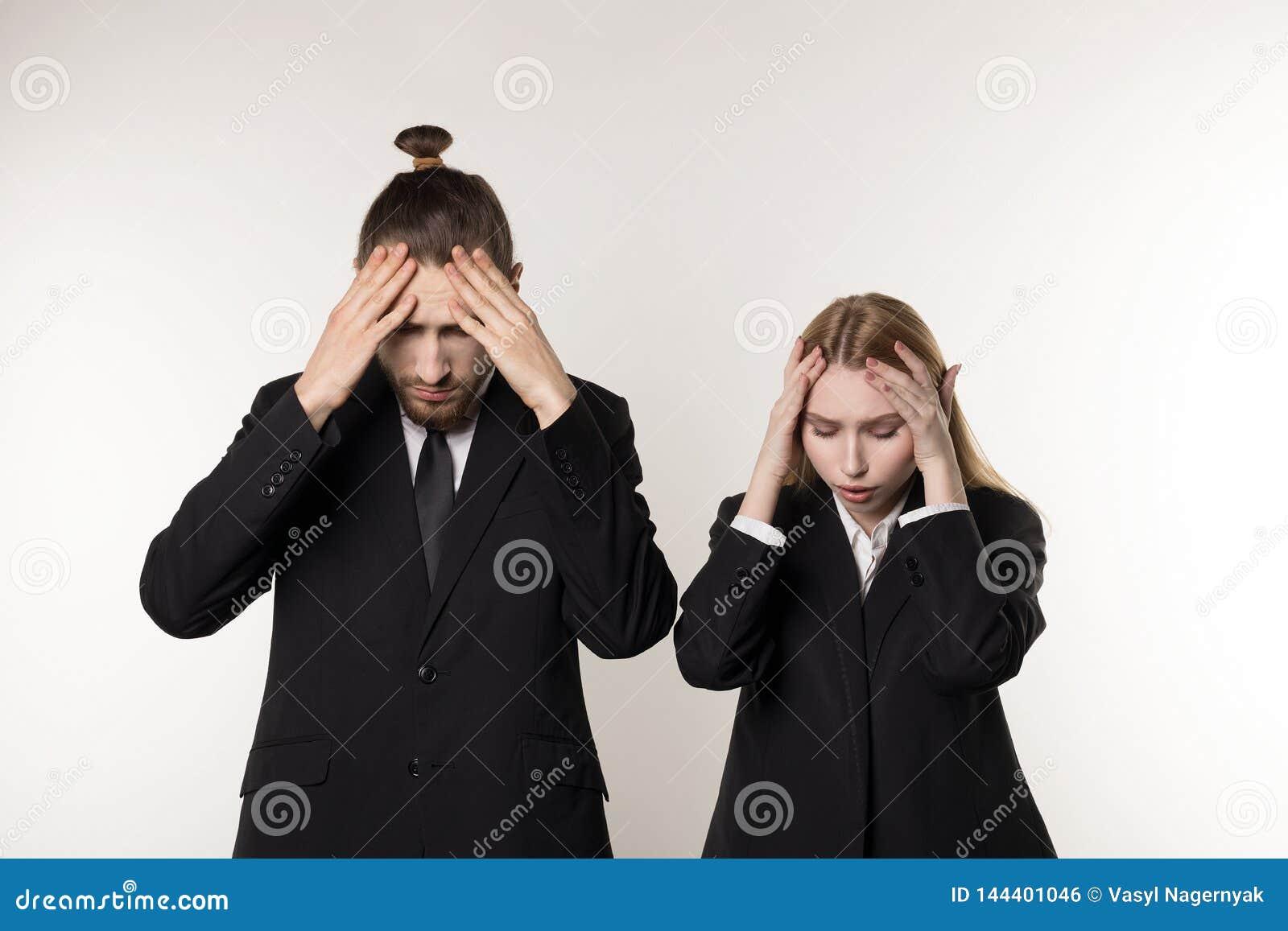 Zwei junge Angestellte in den schwarzen Anzügen, die mit den Händen auf Kopf, entlassene Arbeitskräfte nach Konkurs ihrer Firma s