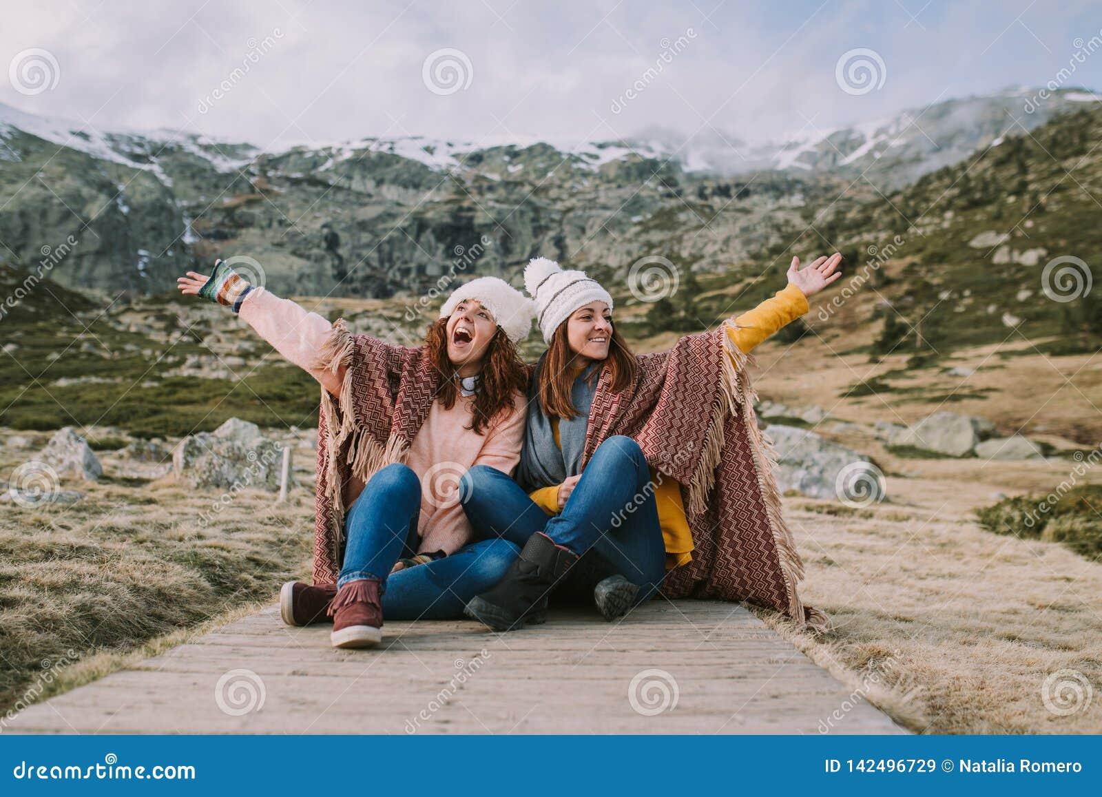Zwei junge Frauen, die auf der Wiese genießt Natur sitzen