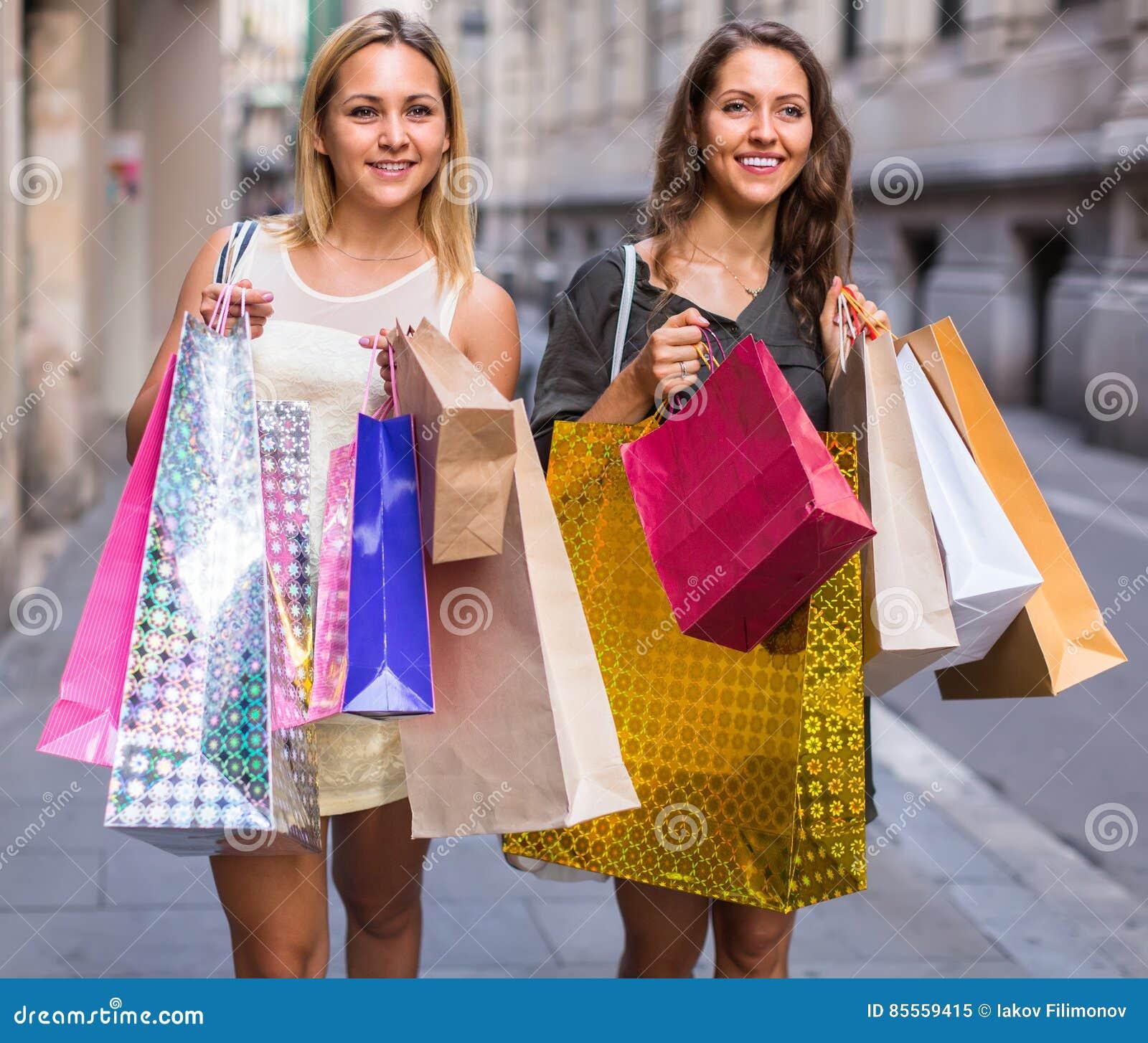 Zwei junge Frauen, die Einkaufstaschen halten