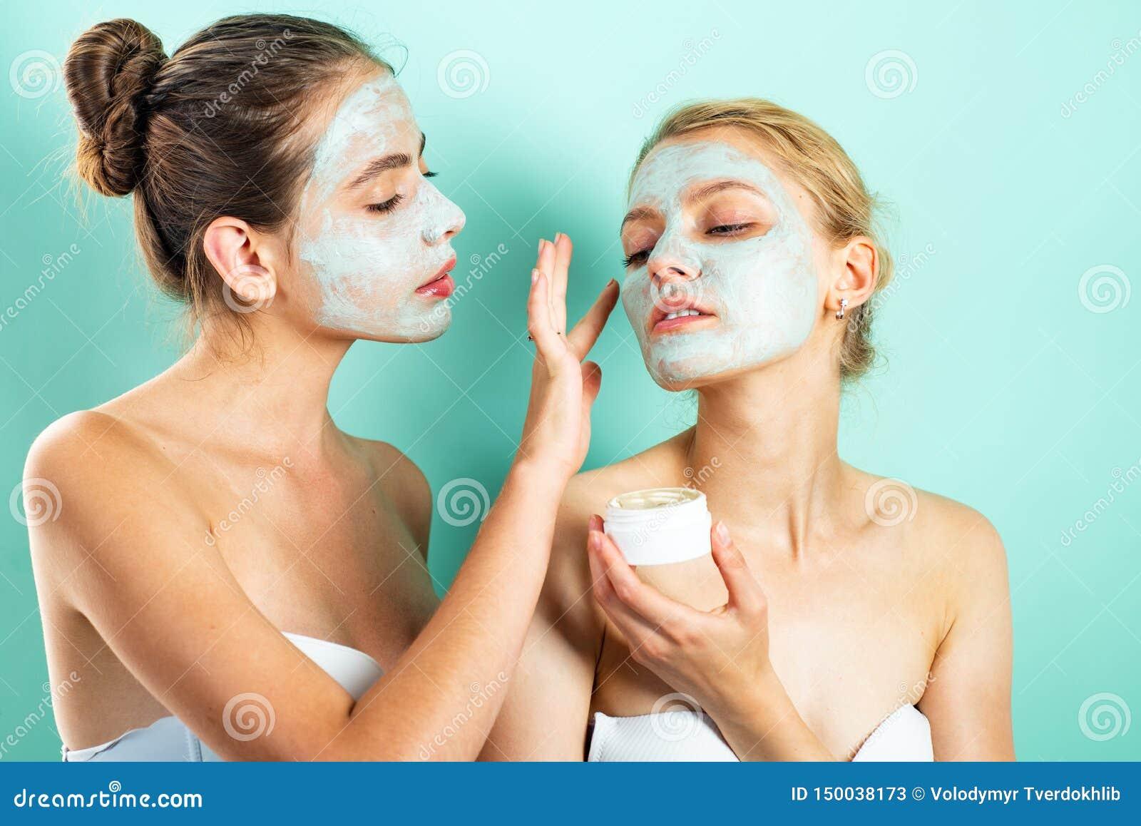 Zwei junge Frauen, die Feuchtigkeitscremecreme auf ihrem Gesicht auftragen Foto von den vorsichtigen Freunden, die Badekuren empf
