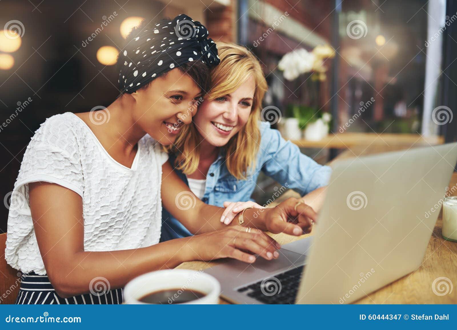 Zwei junge Freundinnen, die das Internet surfen