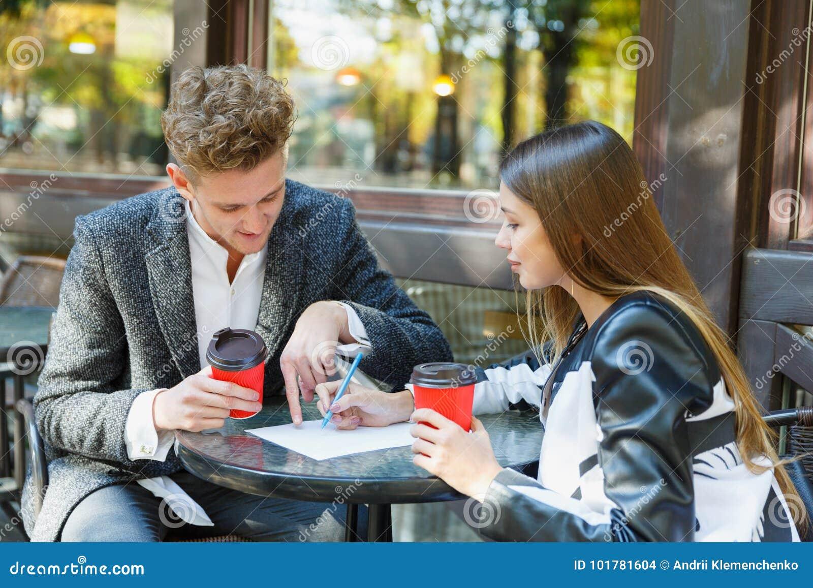 Zwei junge Geschäftsleute, die digitale Tablette auf einer Sitzung an der Kaffeestube verwenden