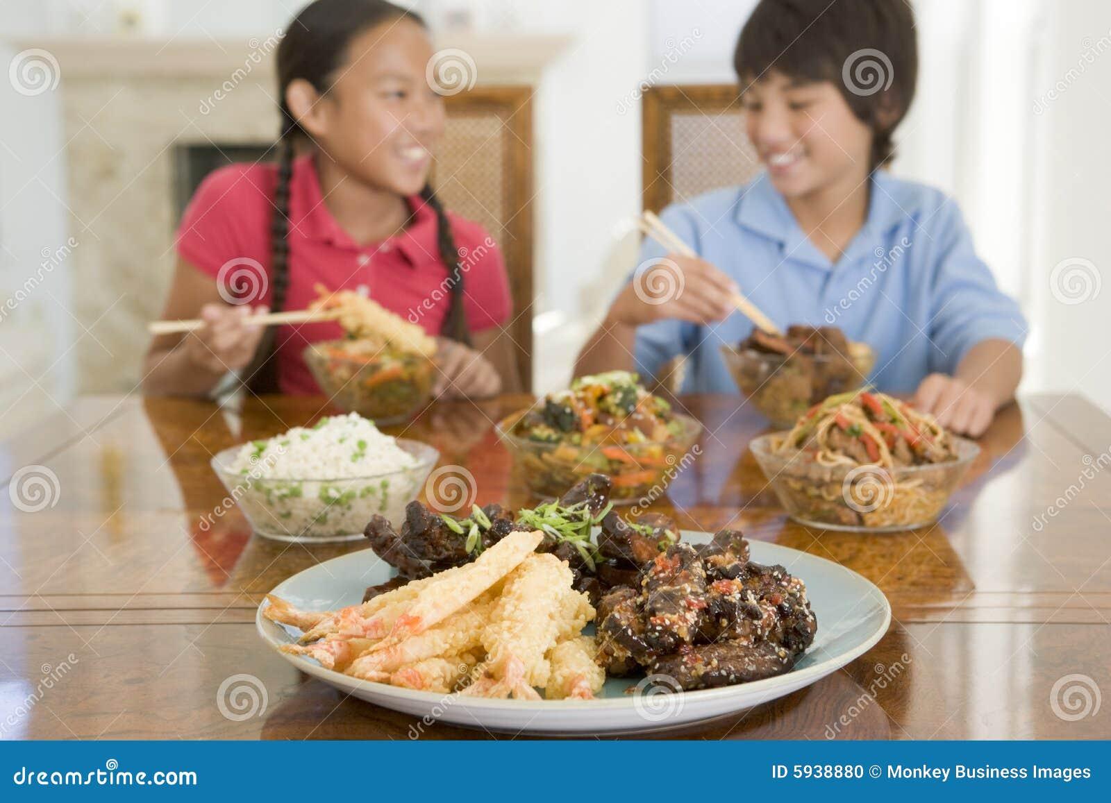 Zwei junge kinder die chinesische nahrung essen stockfoto for Asian cuisine delivery