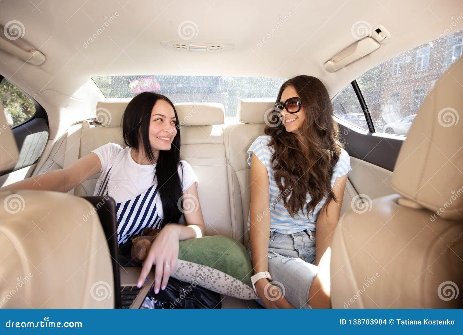 Zwei junge lächelnde schöne Mädchen mit dem langen Haar, gekleidet in der zufälligen Art, sitzen im Rücksitz eines Autos mit a