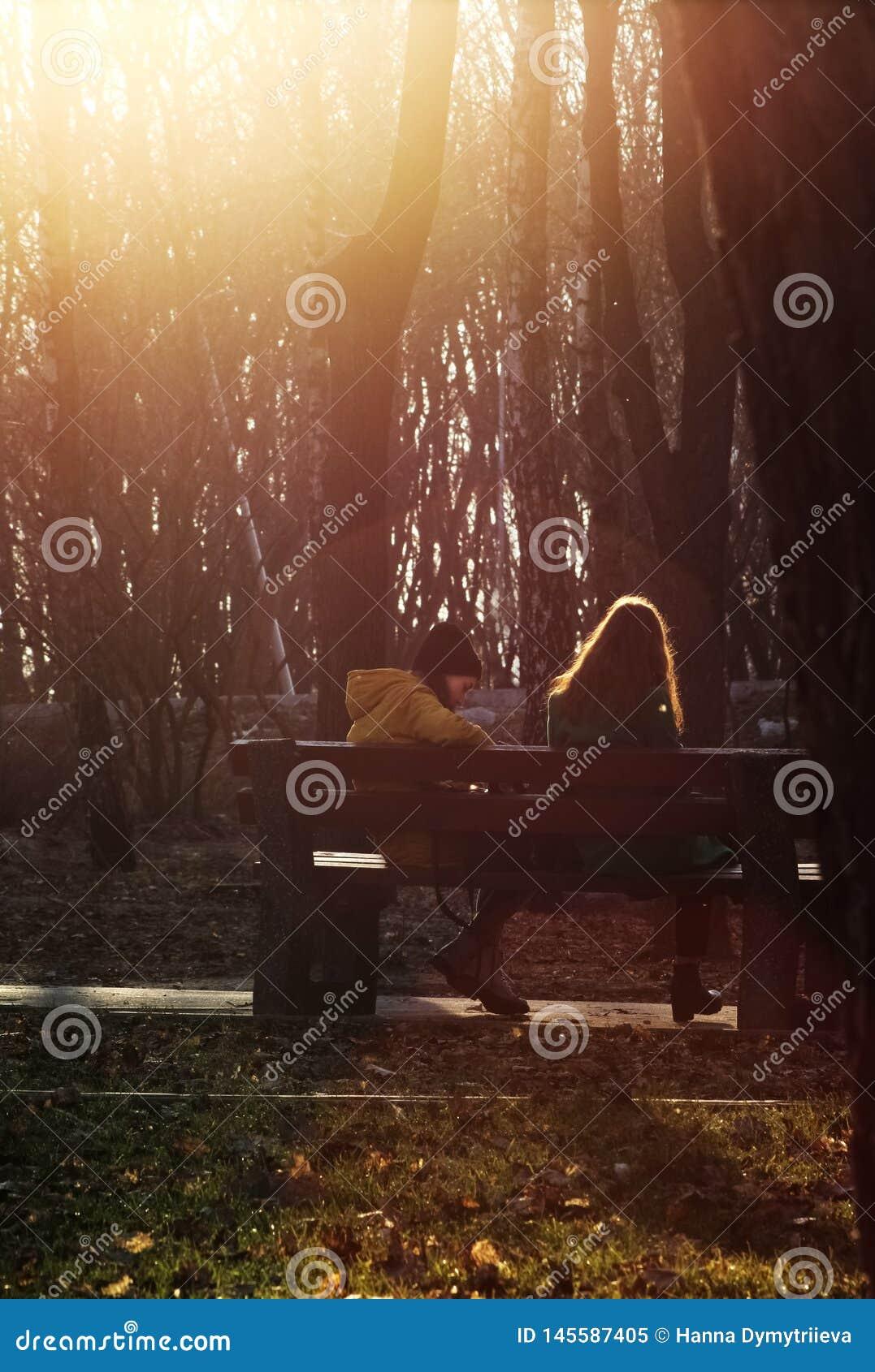 Zwei junge Mädchen, die auf der Bank im Park sprechen Schönes Sonnenuntergang boke