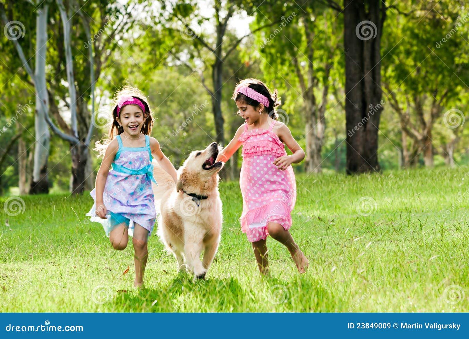 Zwei junge Mädchen, die mit goldenem Apportierhund laufen