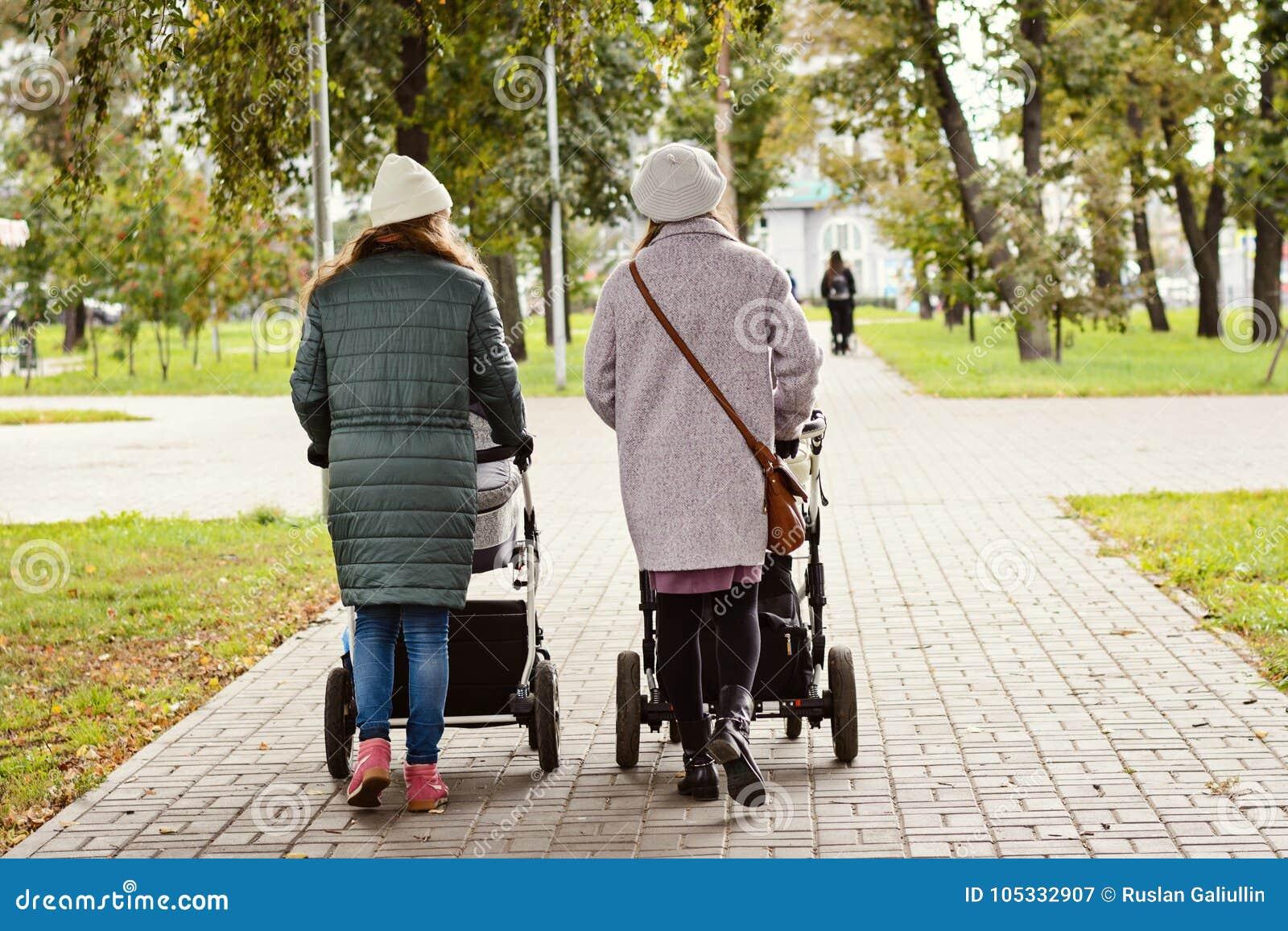 Zwei junge Mutterfreundinnen gehen mit Kleinkindern in den Spaziergängern für einen Herbst Park Frauen auf einem Weg mit den Kind