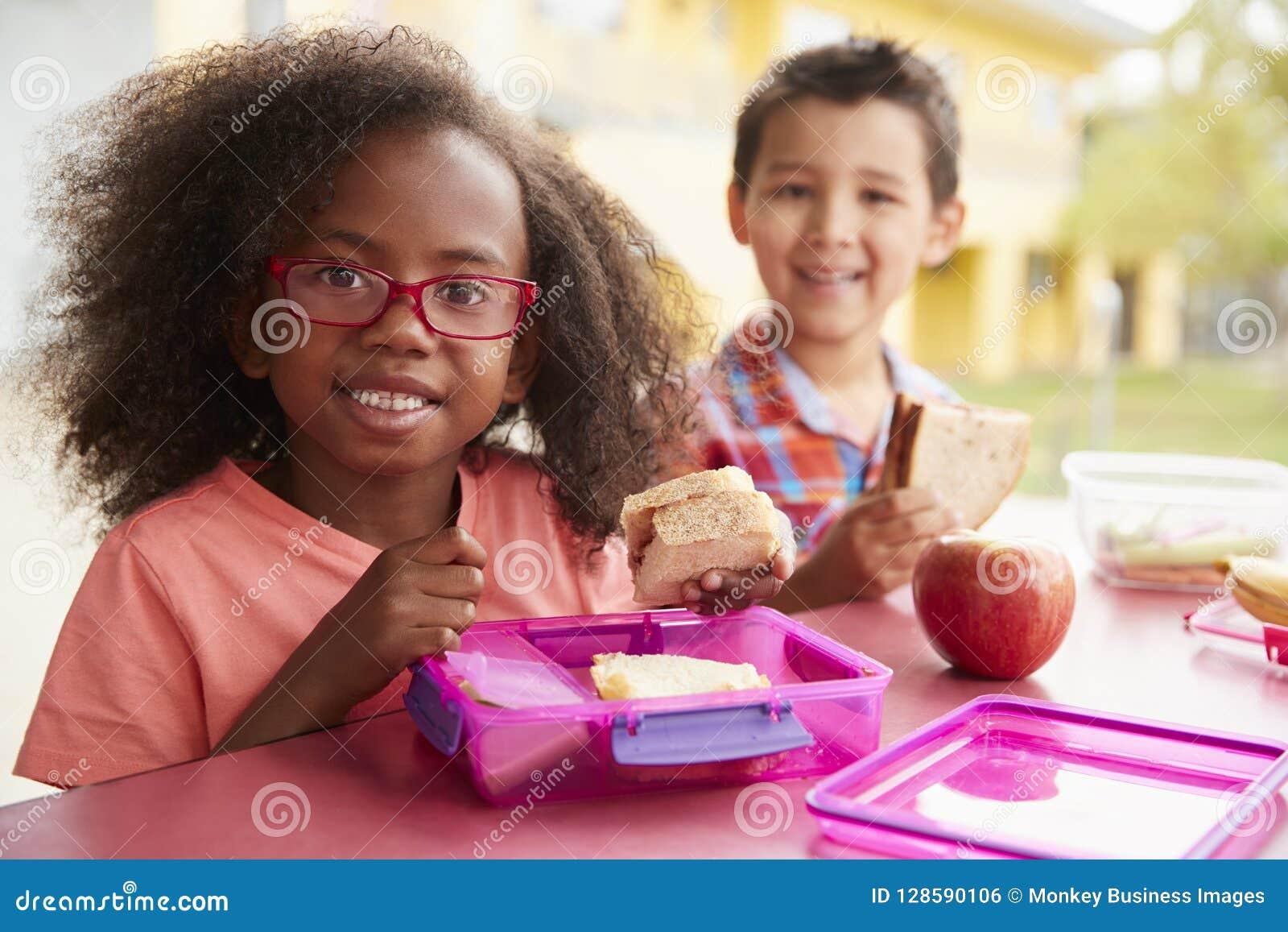 Zwei junge Schulkinder, die zusammen ihre Lunchpakete essen