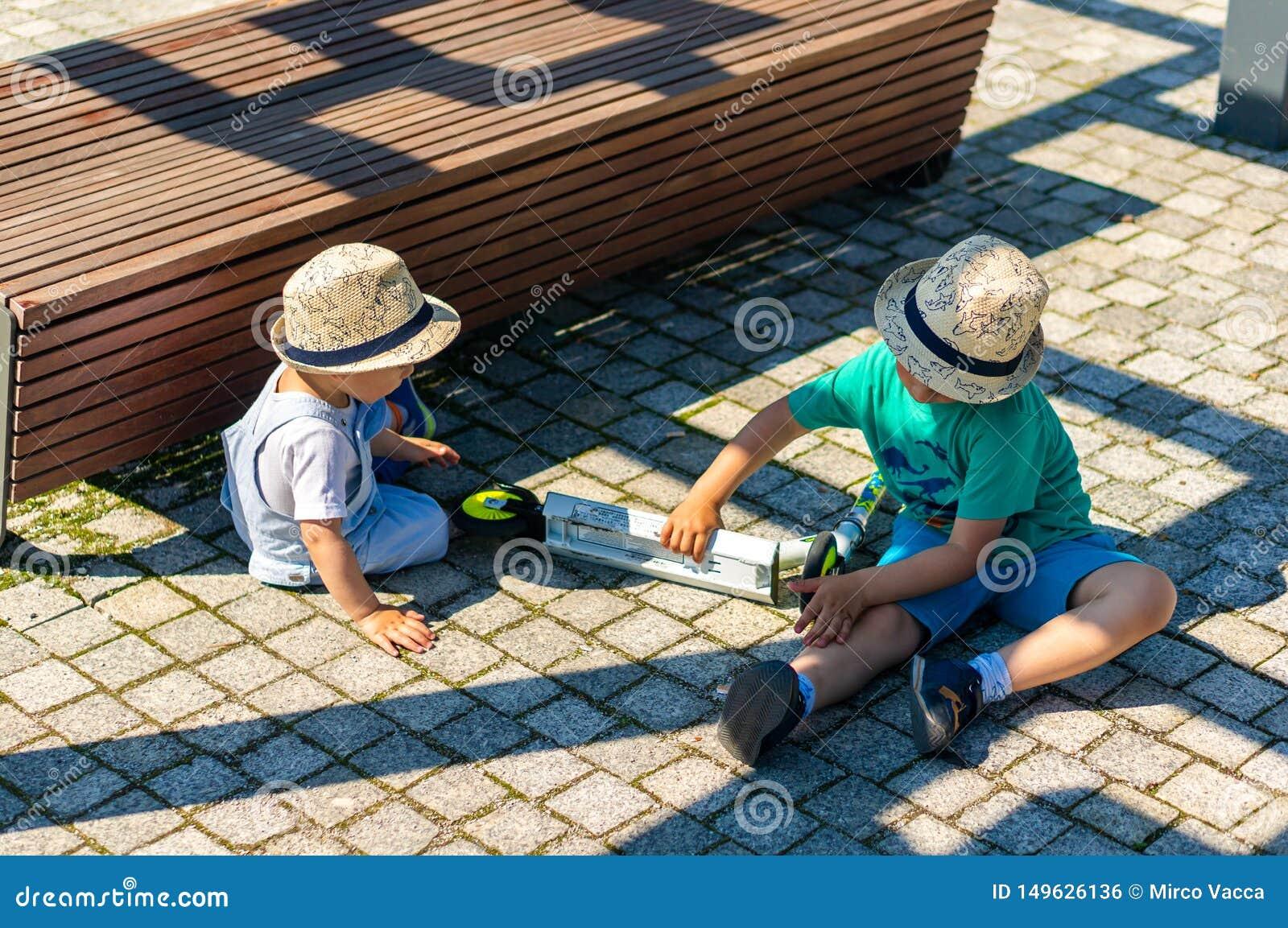 zwei jungen die aus den grund spielen redaktionelles foto