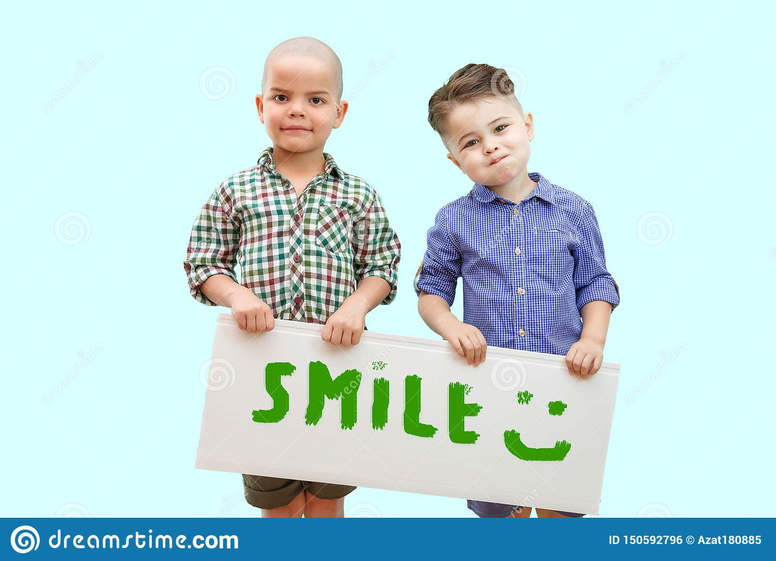 Zwei Jungen, die ein Zeichen halten, das Lächeln sagt