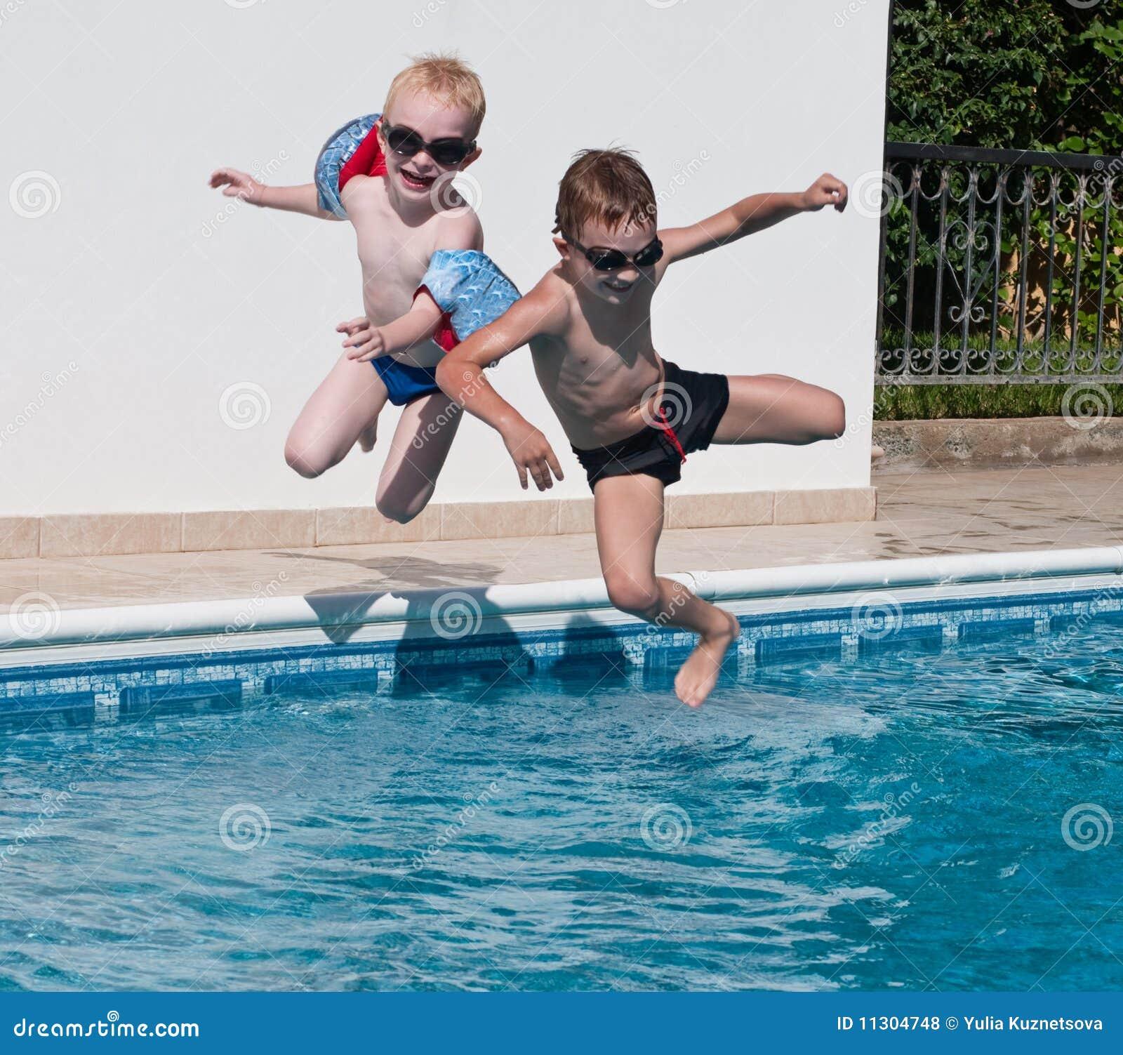 Zwei Jungen, die in Swimmingpool springen